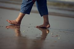 Walking in the sand with dirty feet. stock photos