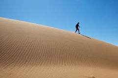 Walking on sand dune. Silhouette walking down sand dune in the summer royalty free stock images