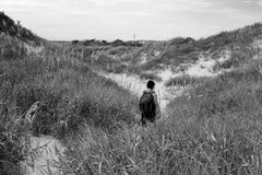 Walking through the Sand dunes at a beach with grass and cloudy skies royalty free stock photo
