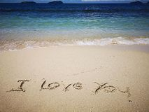Walking on sandy beach and beautiful sunny day and I love you written on the the sandy beach stock images