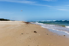Walking on the sandy beach. With a rough sea on the side Stock Image