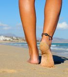 Walking sandy foot. Sandy foot walking on the beach at the shore with a anklet on the left feet Stock Photography