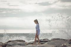 Walking on sea shore. Young woman walking on stony sea shore Stock Photo