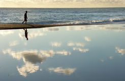 Walking between sea and sky. Young man walking on the beach Stock Photo