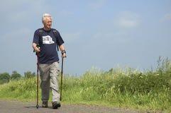 Walking Senior. Senior man doing a Nordic Walk on a sunny day royalty free stock image
