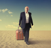 Walking senior man with suitcase in a desert Royalty Free Stock Image