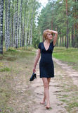 Walking with shoes in hand. Girl with shoes in hand on the forest road Royalty Free Stock Photos