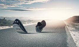 Walking shoes. Pair of black shoes walking on road Stock Image