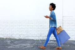 Walking with shopping bags and listening to music Stock Photography