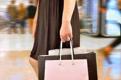 Walking at the shopping mall. Cropped shot of a young woman shopping and walking at the shopping mall. Concept of a shopaholic Royalty Free Stock Image