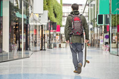 Walking through a shopping mall. Young man, carrying a skateboard, walking casually through a modern shopping mall Stock Photo