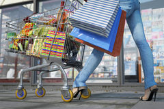 Walking shopping woman holding bag and shopping trolley close up Stock Photos