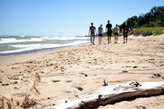 Walking on the Shoreline of Lake Michigan - Indiana Dunes State Park. Friends walking along the beach on the shoreline of Lake Michigan at Indiana Dunes State Royalty Free Stock Image