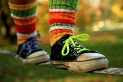 Walking the slackline in sneakers and colour socks. Legs of a girl walking a slackline with a colour socks and sneakers Royalty Free Stock Photos