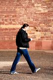 Walking sms man. Man is walking a typing on his cellphone an sms Royalty Free Stock Image
