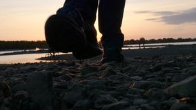 Walking in sneakers on a rocky terrain by the river. HD, 1920x1080. slow motion. stock video footage