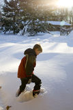Walking through snow. A child walks on a snowy hill stock image