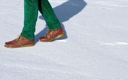 Walking on snow. Girl walking on the snow leaving tracks on the snow of the shoes behind royalty free stock photography