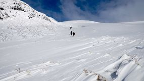 Walking in the snow in Scotland. 3 people walking in the snow in Scotland royalty free stock images