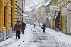 Walking in the snow. Zagreb - 2014 December 28. People walking to work in the street in a snowstorm. Some people sheltering from wind and snow using umbrella Royalty Free Stock Images