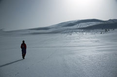 Walking in the snowy mountains. Lonely person walking on the snowy mountain stock image