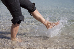 Walking and splashing on sandy beach Royalty Free Stock Photo