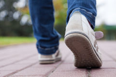 Walking in sport shoes on pavement Stock Images