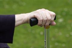 Walking stick grip. Elderly womans hand on walking stick handle royalty free stock photos