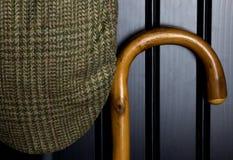 Walking Stick and Tweed Cap on Black Cupboard Door. Walking stick and tweed cap hanging on black cupboard door stock photo