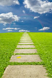 Walking stone to sky and rainbow. Walking stone on grass to sky and rainbow royalty free stock images