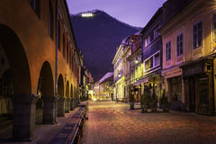 A walking street in downtown medieval city of Brasov, Romania. December 2nd, 2015 with the Tampa mountain in the background. Historic medieval city of Brasov Stock Photos