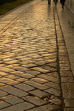 Walking a street of gold. Walk on an old golden cobblestone street at night stock images