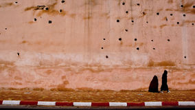Walking. In the streets of Asilah, Morocco. Wall full of holes Stock Image