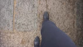 Walking in the streets. Man walking in the streets with black trousers and black shoes stock footage