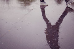 Walking student. Reflection in the wet surface. Royalty Free Stock Image