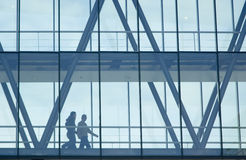 Walking students. Man and woman walking and talking in a glass architectural structure royalty free stock images