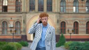 Walking stylish man with beard touching his ginger curly hair at the background of the building. He is wearing striped stock video