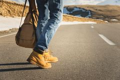 Walking on the summer sunset on the asphalt, men`s legs in yellow shoes and blue jeans go along the asphalt. Next to the royalty free stock photography