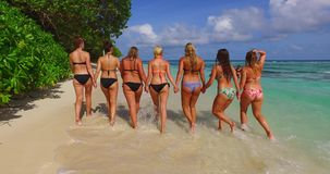 V12800 walking and sunbathing group of young beautiful girls on white sand beach in aqua blue clear sea water and sky Stock Photos