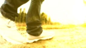 Walking on a sunny day. Legs are walking along the road. Legs are walking along the road. Walking on a sunny day stock footage