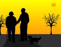 Walking into the sunset.... A elderly couple out walking their dog, and helping  each other, as the sun sets on another beautiful day, together Royalty Free Stock Images