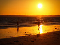 Walking on the sunset. People walking on the sunset, on the beach Royalty Free Stock Photos