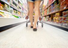 Walking through Supermarket Aisle with a boy on the Shopping Cart royalty free stock image