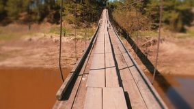 Walking on a suspended wooden bridge over the river. First person view. Walking on a suspended wooden bridge over the river. First person view stock video footage