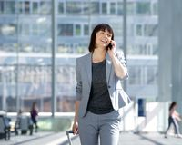 Walking and talking with mobile phone at airport Royalty Free Stock Image