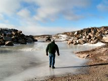 Walking on thin ice. A man crosses thin ice to return to vehicle Royalty Free Stock Image