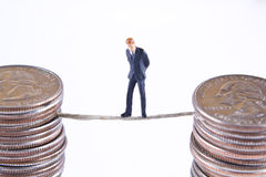 Walking a thin line. Miniature businessman on rope suspended between two stacks of quarters Stock Image