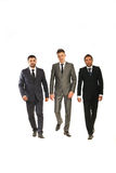 Walking three business men. Three business men walking isolated on white background Stock Image