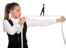 Walking A Tightrope. Business woman walking along a tightrope, isolated on a white background Royalty Free Stock Image