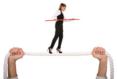 Walking A Tightrope. Business woman walking along a tightrope, isolated on a white background Royalty Free Stock Photos